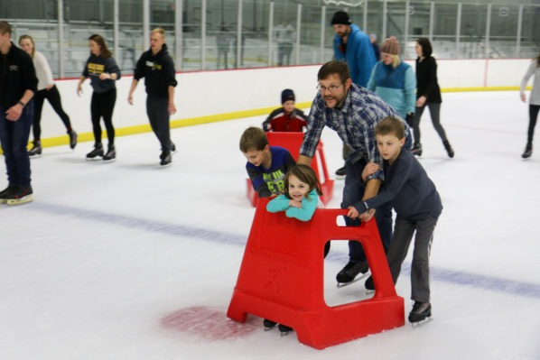 Father ice skating with his kids