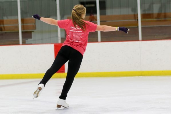 Girl in red t-shirt at figure skating practice.